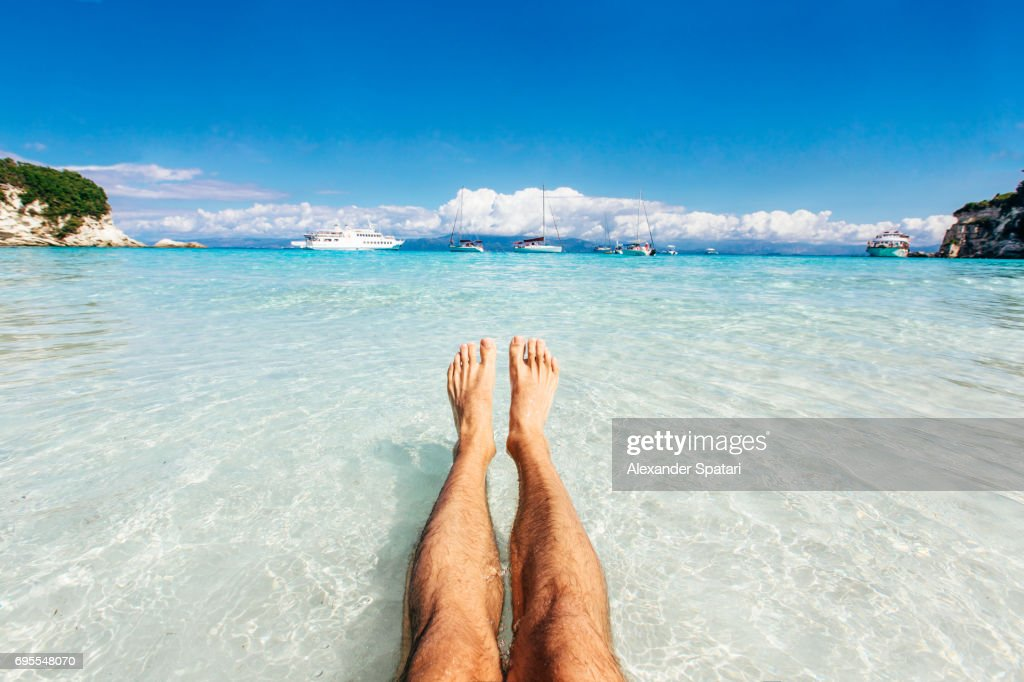 Personal perspective of man's feet in clear turquoise water : Stock Photo