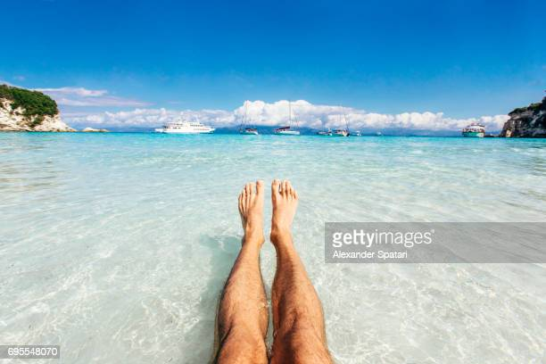 personal perspective of man's feet in clear turquoise water - male feet stock photos and pictures