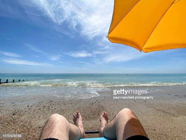 "personal perspective of mans feet looking out to sea - ""paul mansfield photography"" stock pictures, royalty-free photos & images"