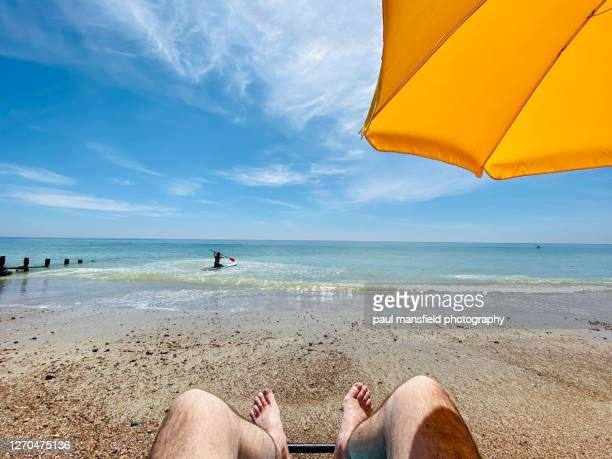 "personal perspective of mans feet looking out to sea with paddle boarder - ""paul mansfield photography"" stock pictures, royalty-free photos & images"