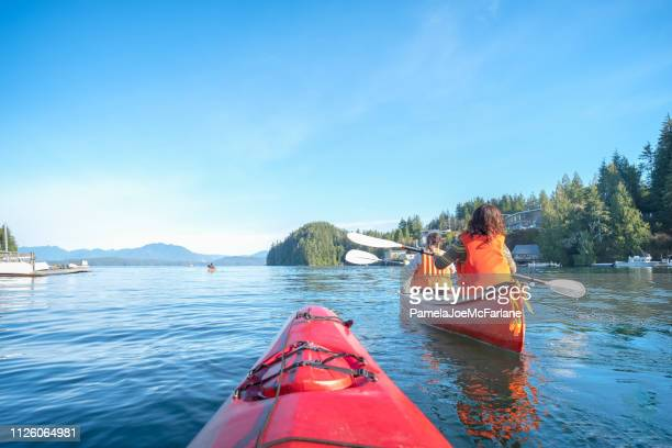 personal perspective of ocean kayaker following multi-ethnic family in canoe - kayak stock pictures, royalty-free photos & images