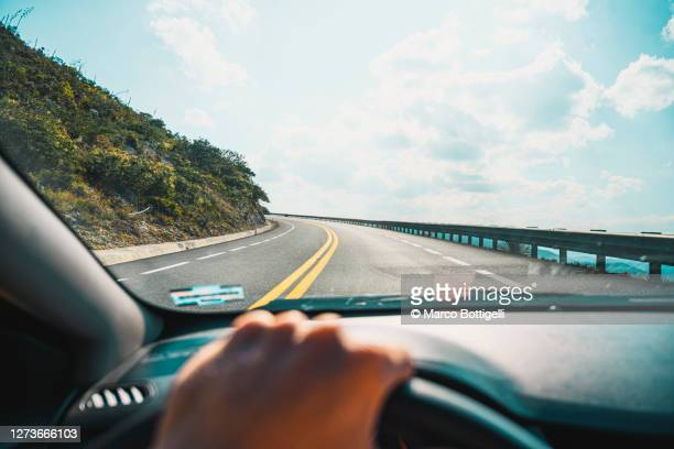 personal perspective of person driving on mountain road - road trip stock pictures, royalty-free photos & images