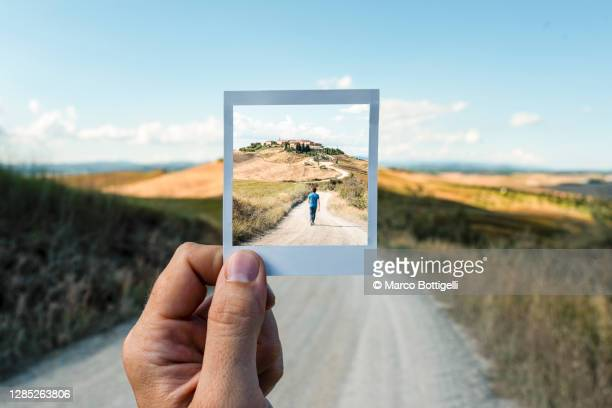 personal perspective of polaroid picture overlapping a country road in tuscany - photography stock pictures, royalty-free photos & images