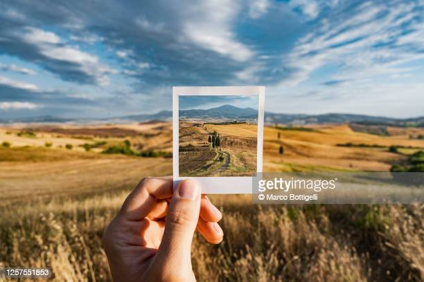 personal perspective of polaroid picture overlapping the tuscany landscape, italy - travel foto e immagini stock