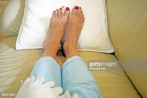 personal perspective of senior woman's feet relaxing on sofa - old lady feet stock pictures, royalty-free photos & images