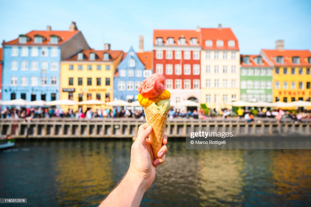 Personal perspective of tourist holding an ice cream in front of Nyhavn canal, Copenhagen : Stock Photo