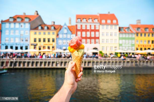 personal perspective of tourist holding an ice cream in front of nyhavn canal, copenhagen - copenhagen stock pictures, royalty-free photos & images