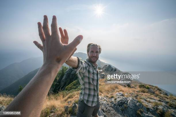 personal perspective of two hikers celebrating on mountain top with a high five - reaching stock pictures, royalty-free photos & images