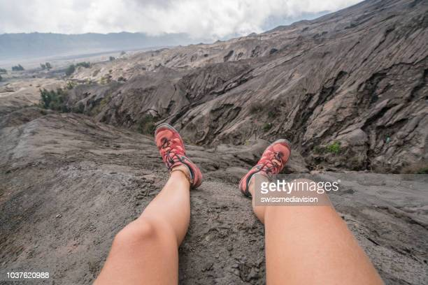 personal perspective of woman hiker resting on mountain trail on crater volcano, bromo national park view, on top of it all. people travel discovery concept  indonesia - bromo crater stock pictures, royalty-free photos & images