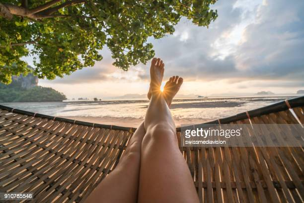 personal perspective of woman relaxing on hammock, feet view - leg stock pictures, royalty-free photos & images