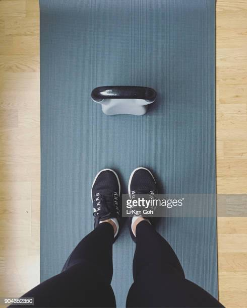 Personal perspective of woman standing on exercise mat with a kettlebell