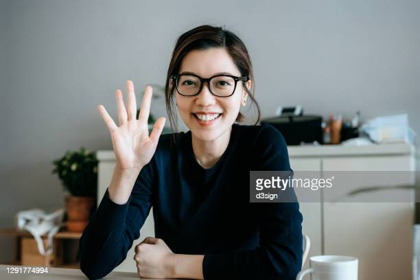 personal perspective of young asian woman working from home, waving hand and talking in front of the camera having video conference with her business partners on laptop at home - waving stock pictures, royalty-free photos & images
