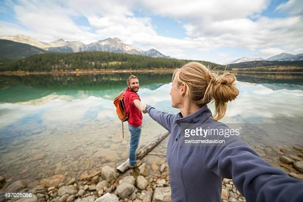 perspective personnelle de jeune couple tenant mains sur le lac