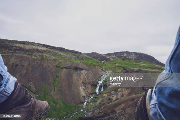 personal perspective of young man and his hiking boots. looking at a hot thermal stream. - sulfuric acid stock photos and pictures