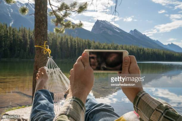 Personal perspective of young man relaxing on hammock and using mobile phone