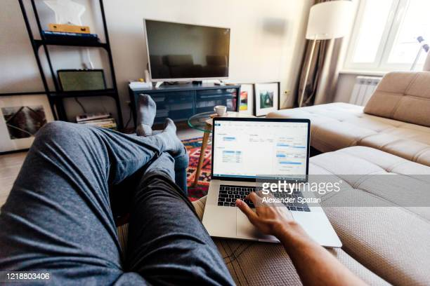 personal perspective point of view of a man working on laptop in the living room at home - standpunt stockfoto's en -beelden