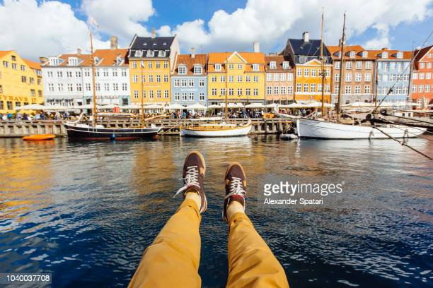 personal perspective point of view of man sitting at the nyhavn canal in copenhagen, denmark - copenhague photos et images de collection