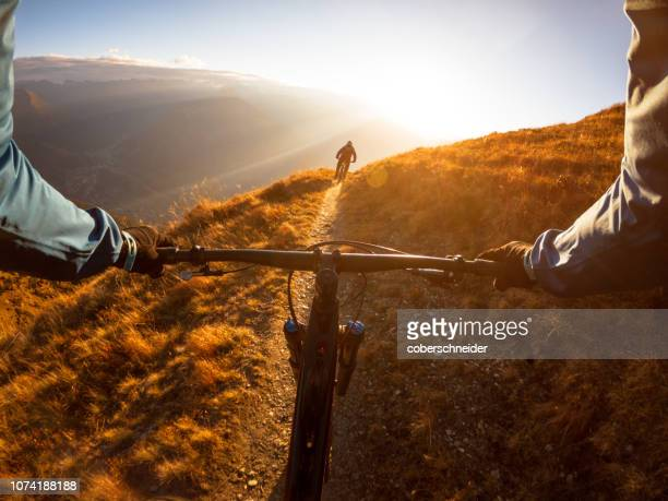personal perspective shot of a man mountain biking with a friend in the alps, gastein, salzburg, austria - ponto de vista - fotografias e filmes do acervo