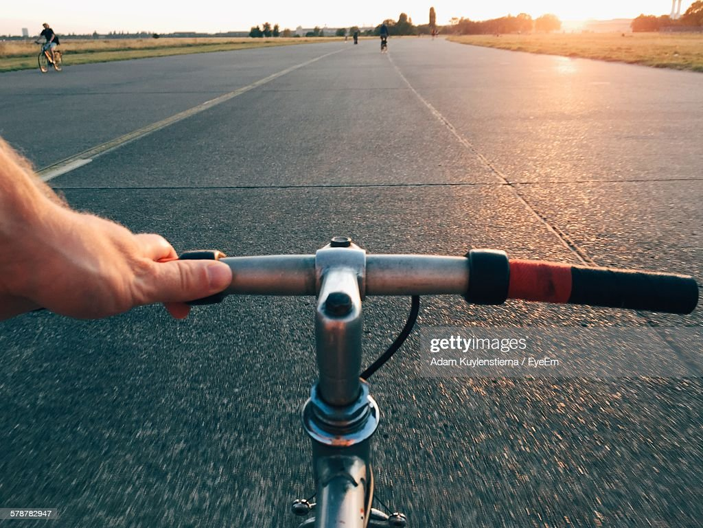 Personal Perspective Shot Of Man Riding Bicycle On Abandoned Airstrip : Stock Photo