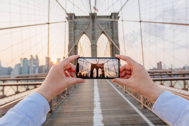 personal perspective view of a man photographing brooklyn bridge using smartphone, new york, usa - 攝影 個照片及圖片檔