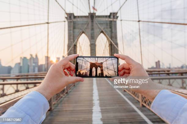 personal perspective view of a man photographing brooklyn bridge using smartphone, new york, usa - photography themes stock pictures, royalty-free photos & images