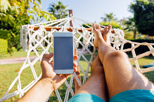 Personal perspective view of a man swinging in hammock and using smart phone - gettyimageskorea