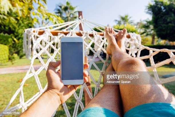 personal perspective view of a man swinging in hammock and using smart phone - legs crossed at ankle stock pictures, royalty-free photos & images