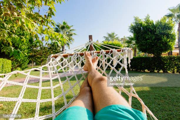 personal perspective view of a young man relaxing in the hammock - point of view stock pictures, royalty-free photos & images