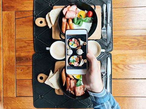Personal perspective view of a young man taking picture with smart phone of a cafe table with breakfast served in skillets - gettyimageskorea