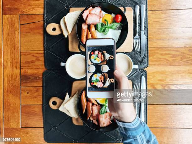 Personal perspective view of a young man taking picture with smart phone of a cafe table with breakfast served in skillets