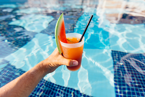 Personal perspective view of drinking watermelon cocktail in swimming pool - gettyimageskorea