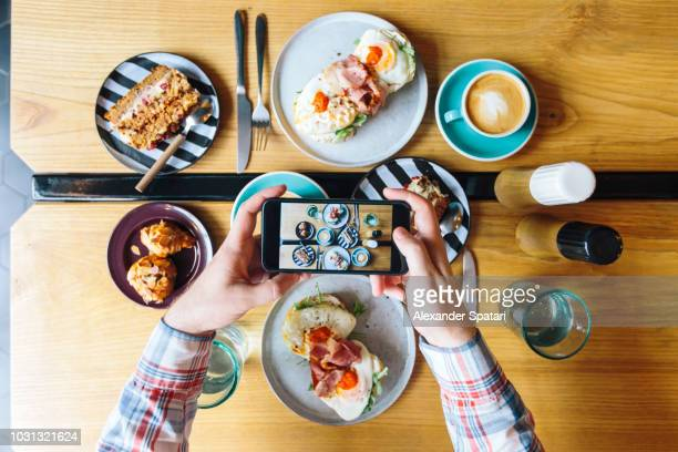 personal perspective view of man photographing his brunch in cafe with smartphone - kaffee getränk stock-fotos und bilder