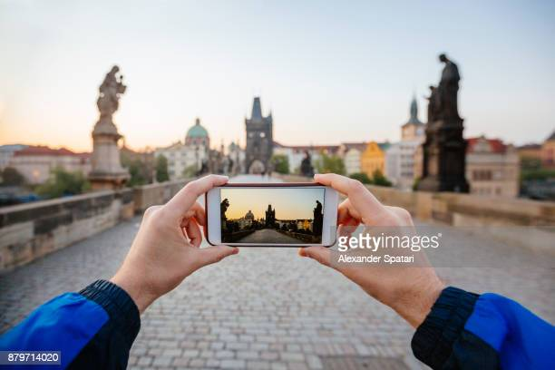 Personal perspective view of man taking pcitres with his phone of Charles Bridge, Prague, Czech Republic