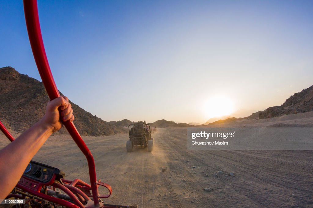 Personal perspective view of mans arm driving beach buggy in desert, Hurghada, Al Bahr al Ahmar, Egypt : Stock Photo