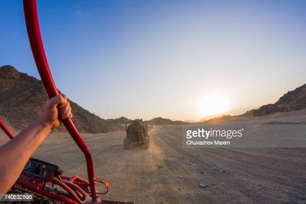 Personal perspective view of mans arm driving beach buggy in desert, Hurghada, Al Bahr al Ahmar, Egypt