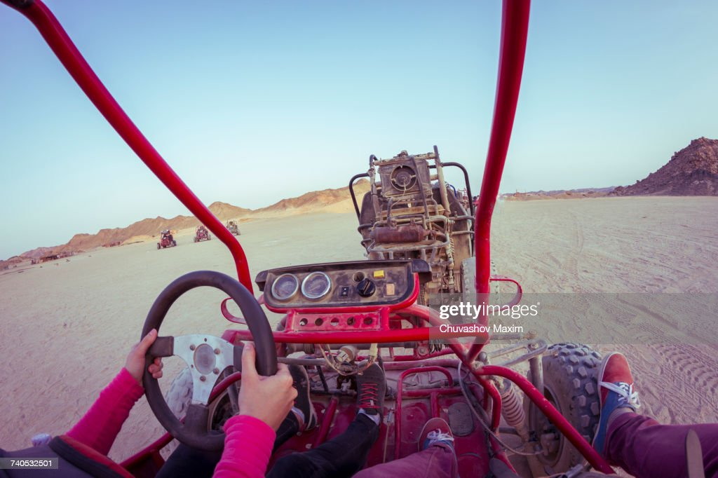 Personal perspective view of two people driving beach buggy in desert, Hurghada, Al Bahr al Ahmar, Egypt : Stock Photo