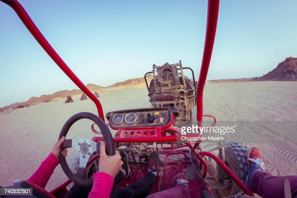 Personal perspective view of two people driving beach buggy in desert, Hurghada, Al Bahr al Ahmar, Egypt
