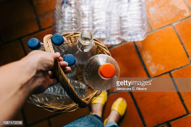 personal perspective woman recycling plastic in basket - recycling stock pictures, royalty-free photos & images