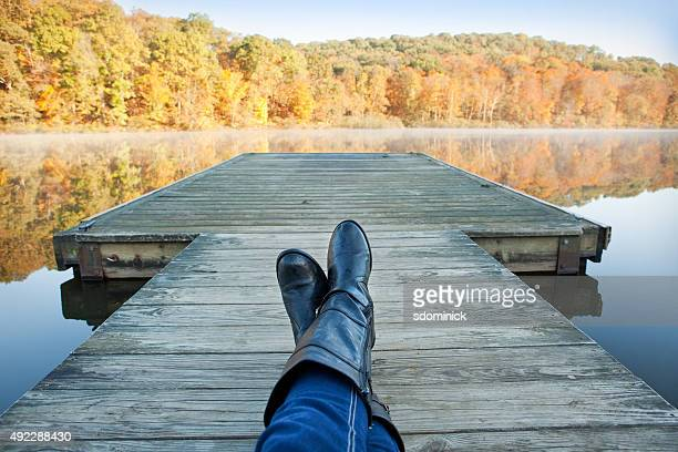 personal perspective woman resting on dock enjoying fall view - mujeres fotos stock pictures, royalty-free photos & images