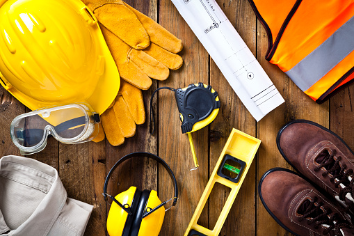 Personal safety workwear and construction blueprint shot directly above 470172604