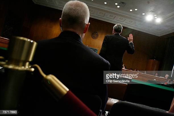 A personal security agent sits close behind FBI Director Robert Mueller as he raises his right hand and swears to tell the truth before testifying to...