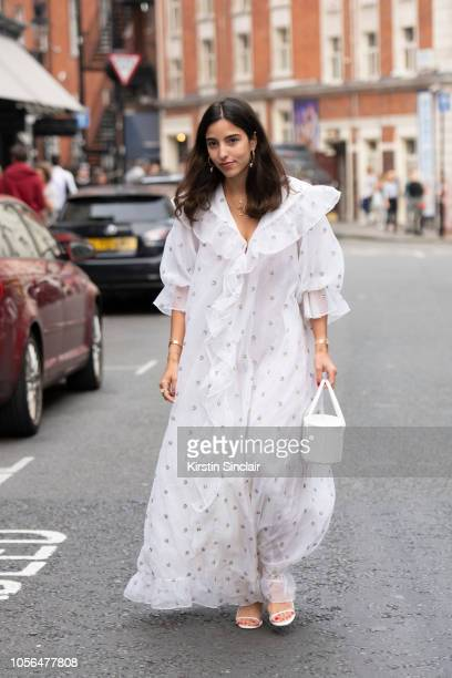 Personal Shopper and digital influencer Bettina Looney wears a WinWingtage dress, Pop and Suki bag, The Row shoes during London Fashion Week...