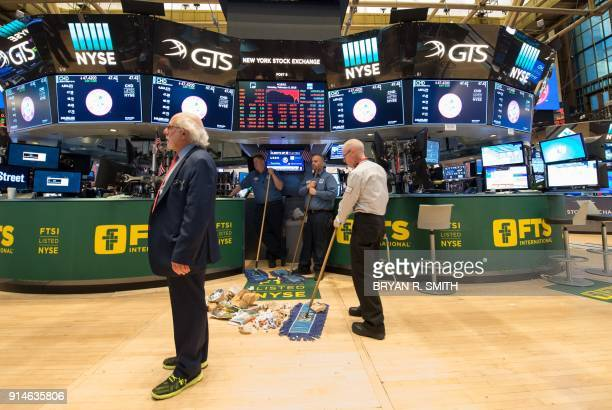 TOPSHOT Personal sweep the floor after the closing bell of the Dow Industrial Average at the New York Stock Exchange on February 5 2018 in New York...