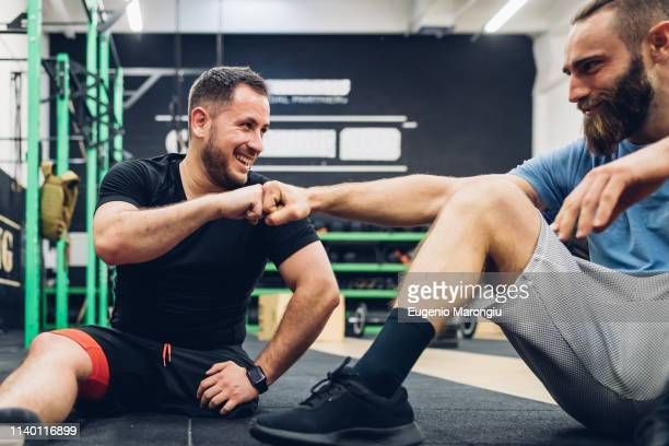 personal trainer and man with disability enjoying conversation in gym - amputiert stock-fotos und bilder