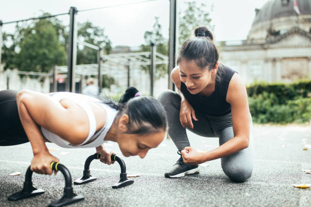 Personal trainer and woman doing freeletics.