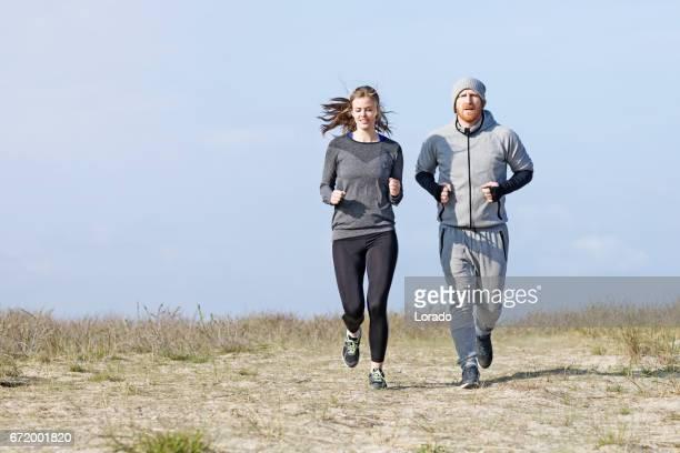 Personal Trainer und junge Sportlerin, die Arbeiten in der Nähe des Meeres
