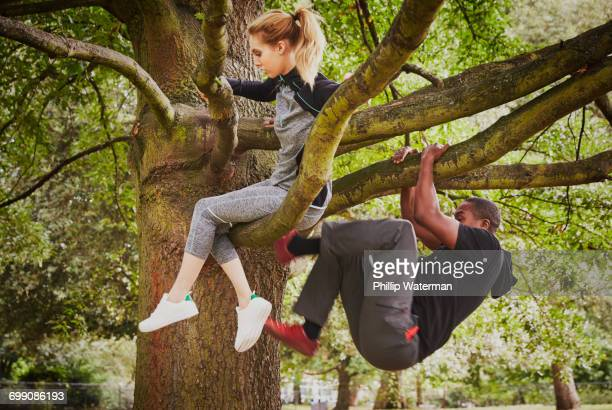 Personal trainer and young woman climbing up park tree