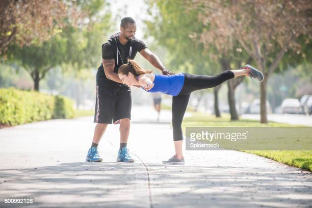 personal trainer assisting client - standing on one leg stock pictures, royalty-free photos & images