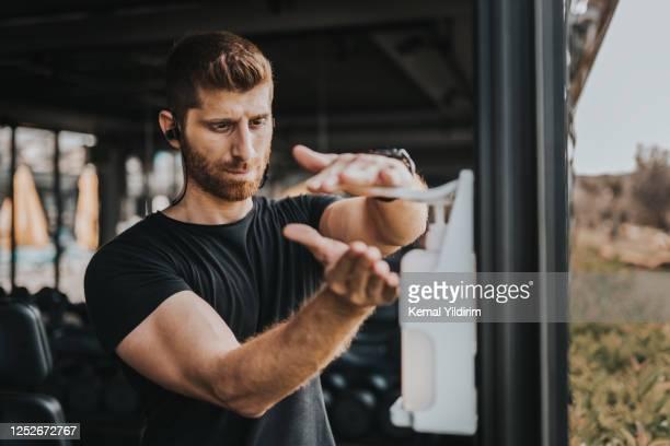 personal trainer cleaning zijn hand met antiseptische tijdens nieuw-normaal - head coach stockfoto's en -beelden