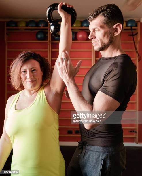 Personal trainer coaches his curvy client in the gym